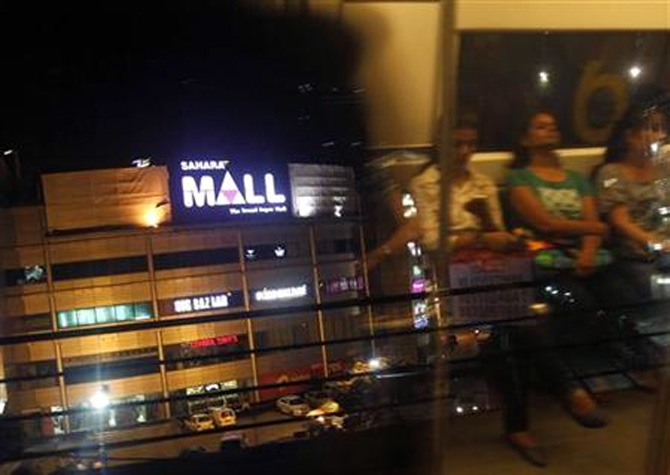 A metro train moves past Sahara Mall, a shopping centre built by Sahara group, in Gurgaon