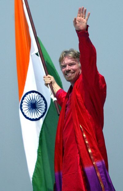 Virgin Atlantic chairman Richard Branson holds Indian national flag on the wing of a Virgin Atlantic aircraft at Bombay international airport.