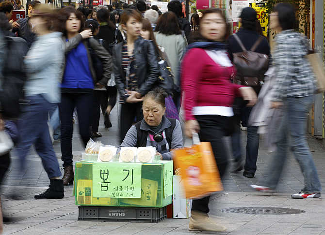 A vendor, selling traditional candies, waits for customers in Myeongdong shopping district in Seoul, South Korea.