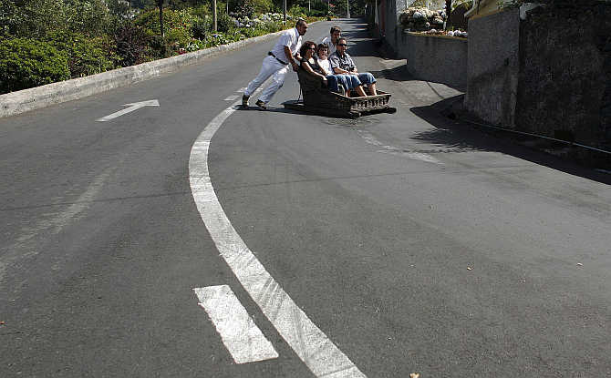 Carreiros (sledge drivers) push tourists in a sledge in Monte on the Atlantic island of Madeira, Portugal.