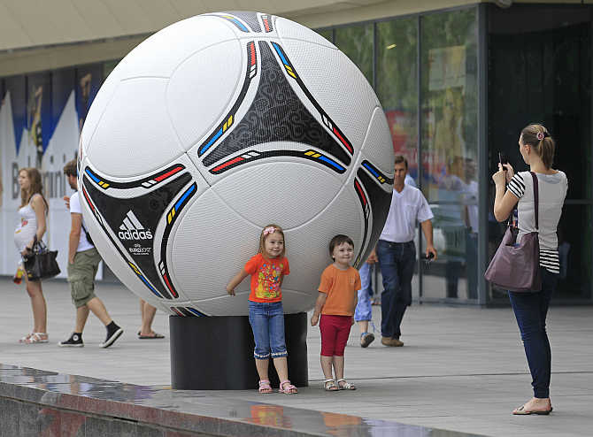 A woman takes photos of her children near a giant soccer ball outside of a shopping mall in central Donetsk, Ukraine.