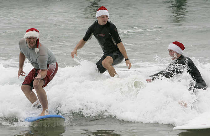 Tourists wearing Santa Claus hats try surfing at Manly Beach in Sydney, Australia.