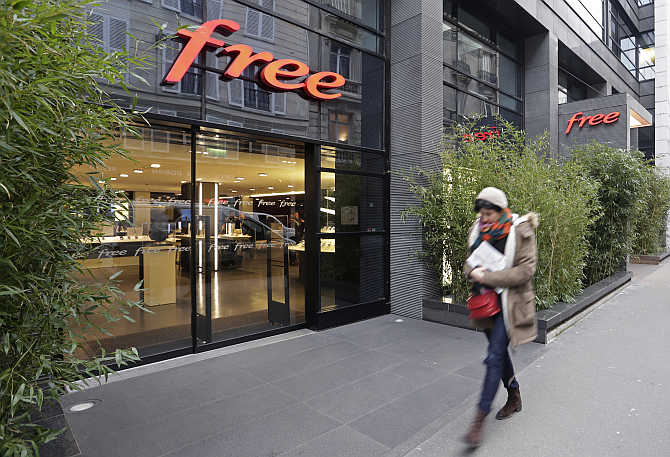 A woman walks past French Internet service provider and mobile phone operator Free's store in Paris, France.
