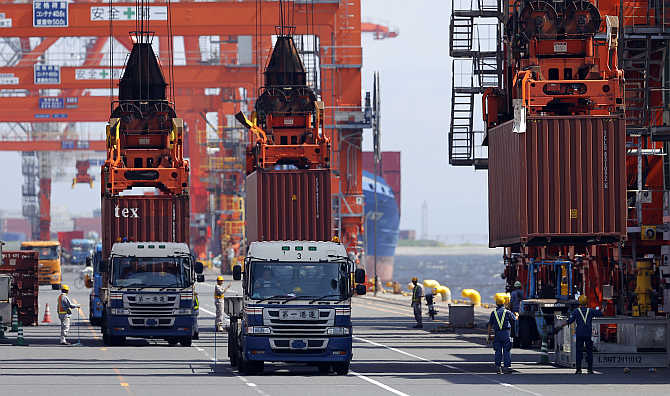 Workers load containers from trucks onto a cargo ship at a port in Tokyo, Japan.