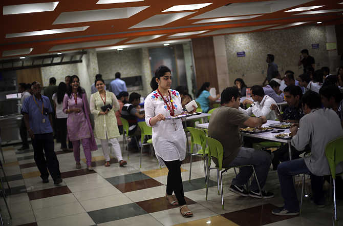 An employee carries her lunch at a cafeteria inside Tech Mahindra office building in Noida.