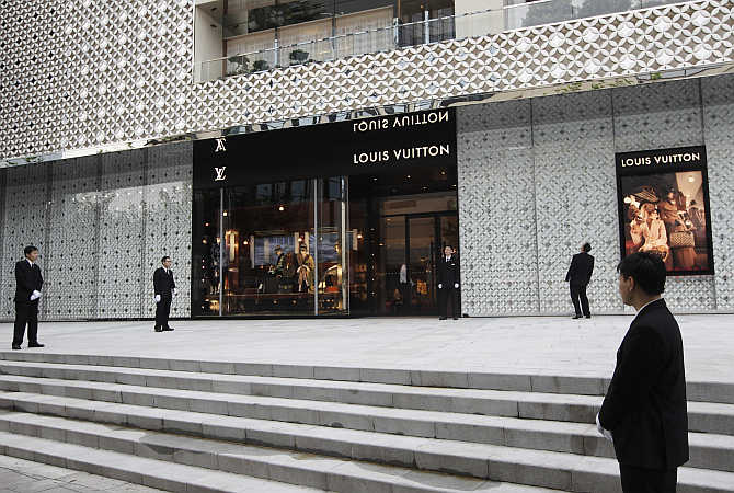 Security guards stand in front of the largest Louis Vuitton store in China, in Shanghai.