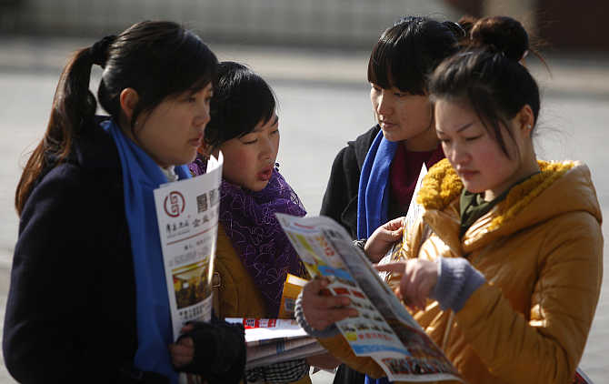 Job seekers look at employment information during a job fair in Shanghai, China.