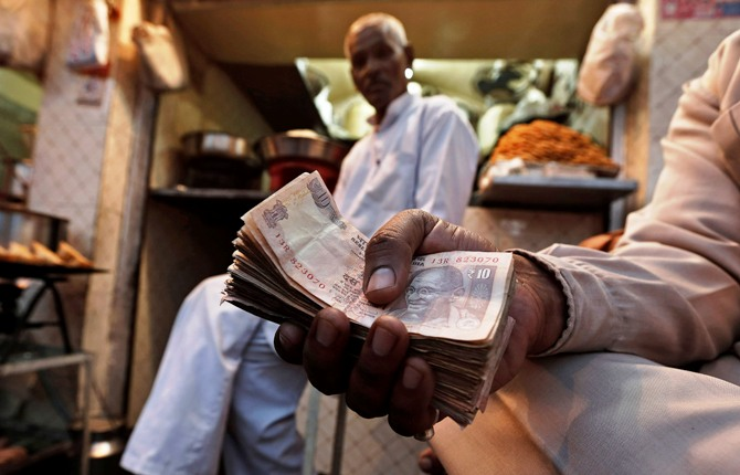 A street side restaurant owner holds a bundle of Indian currency notes as he sits outside his restaurant in New Delhi.