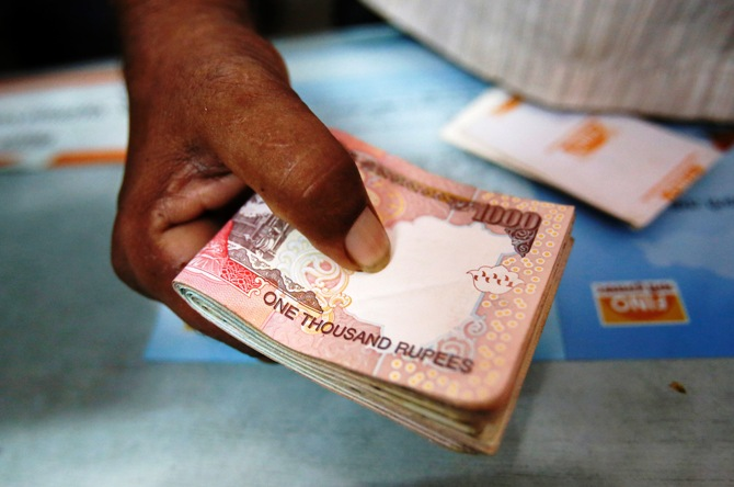 A customer hands a bundle of Indian Rupee notes to a teller at a financial institution in Mumbai.