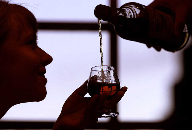 A woman extends her glass for whisky in Edinburgh, Scotland.