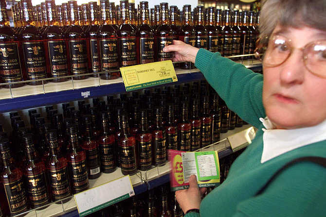 A shopper picks a bottle of whisky at the Duty Free shop at the Channel Tunnel Terminal in Coquelles, northern France.