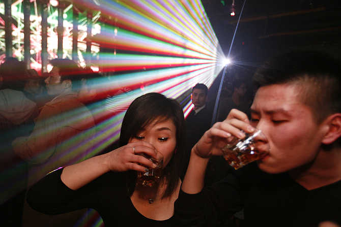 Guests drink next to the dance floor during a night out in Shanghai, China.