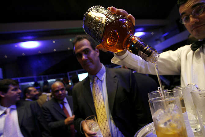 A waiter pours whisky during a Venezuelan-American Chamber of Commerce party in Caracas, Venezuela.