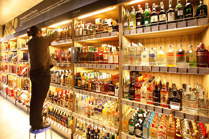 An employee arranges bottles of whisky at a supermarket.