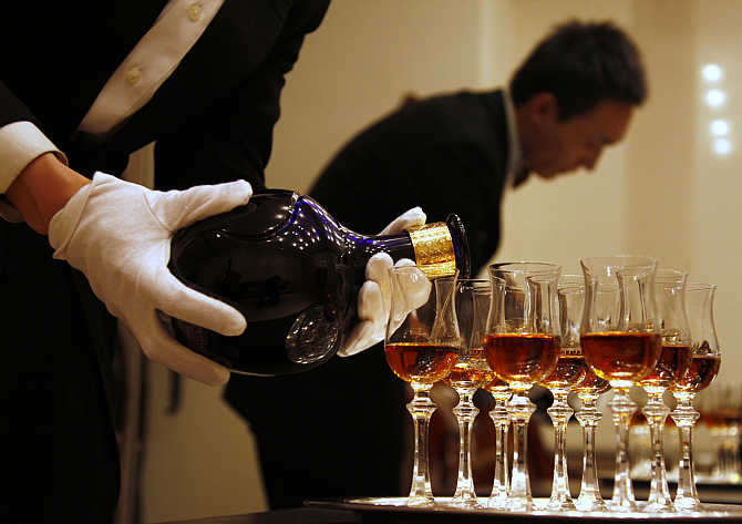A waiter is reflected in a mirror as he pours whisky in Beijing, China.