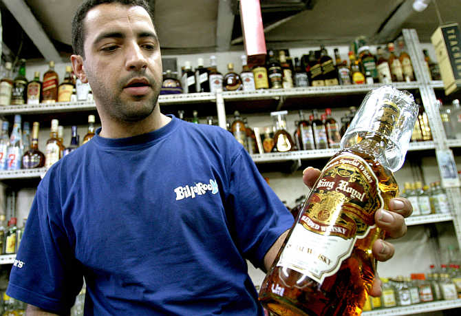 A vendor shows a bottle of whisky.