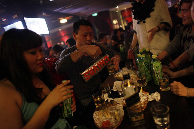 A man pours whisky from a jug at a bar in a nightclub in Shanghai, China.