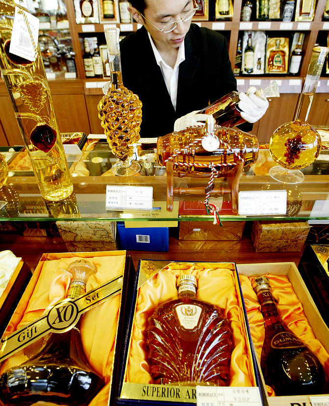 A salesman arranges a display of whisky bottles in a liquor shop.