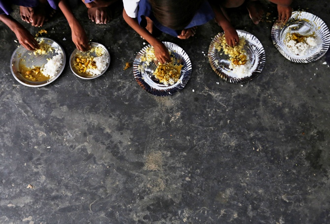 Schoolchildren eat their free mid-day meal, distributed by a government-run primary school at Brahimpur village in Chapra district of Bihar.