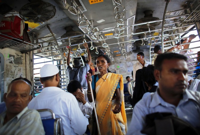 A blind woman begs for alms inside a commuter train during the evening rush hour in Mumbai.