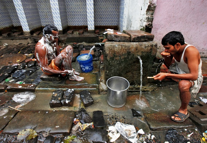 Men bathe at a roadside municipal tap in Kolkata.