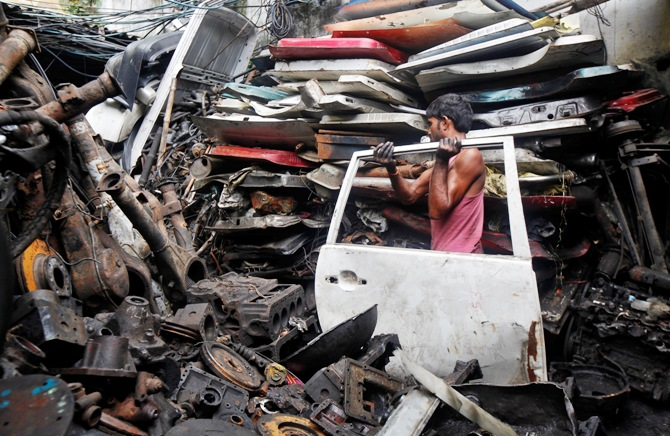 A labourer carries the door of a car inside a second-hand automobile parts market in Kolkata.