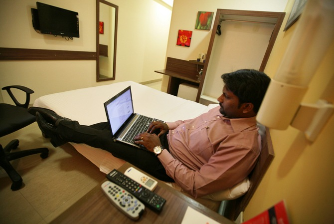 A guest works on a laptop inside his room at the Tata Group's Indian Hotels Co. Ginger chain in Ahmedabad.