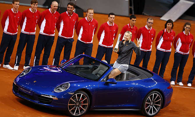 Russia's tennis player Maria Sharapova celebrates after winning a Porsche 911 4S in Stuttgart, Germany.