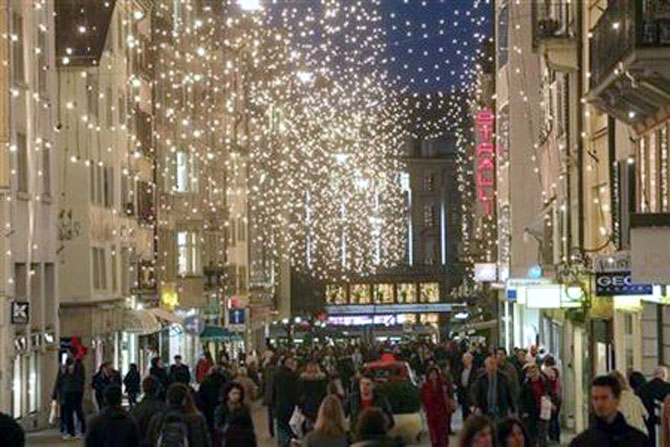 Shoppers walk under Christmas illuminations on Rennweg street in Zurich.