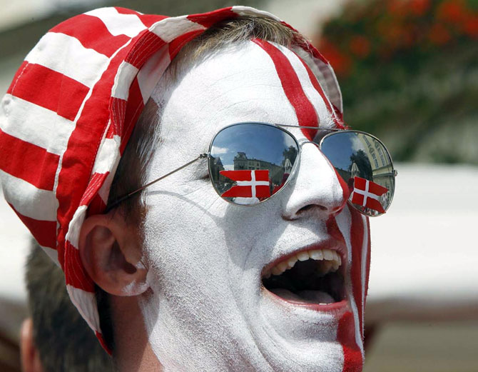 A Denmark soccer fan with his face painted in national colours.