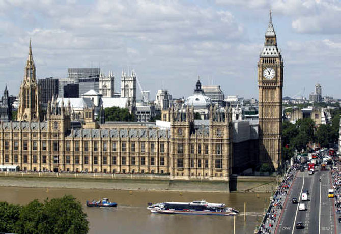 Traffic on the road and the Thames passes the Houses of Parliament in London.