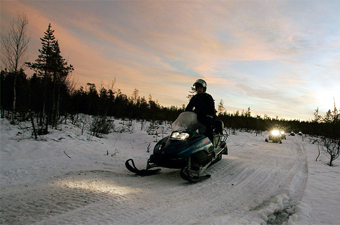 Tourists drive snowmobiles during an arctic safari at Arctic Circle near Rovaniemi, northern Finland.