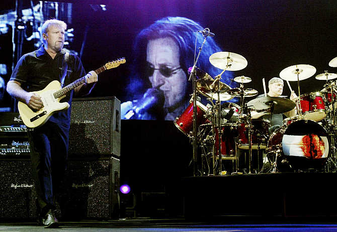 Rush guitarist Alex Lifeson, left, and drummer Neil Peart, right, perform in front of a video image of singer/bassist Geddy Lee at the MGM Grand Garden Arena in Las Vegas, Nevada.