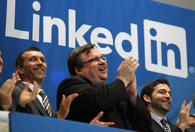 Founder of Linkedin Reid Garrett Hoffmanm, centre, applauds with CEO Jeffrey Weiner, right, from the bell balcony at the New York Stock Exchange.