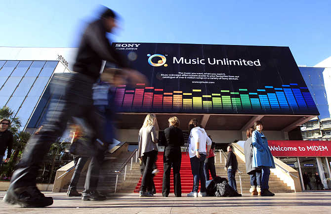 Visitors walk past the record music publishing and video music market in Cannes, France.