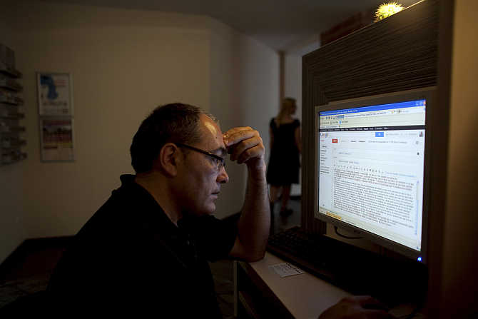 Jose Manuel Abel, 46, writes an email in an Internet cafe in Munich, Germany.