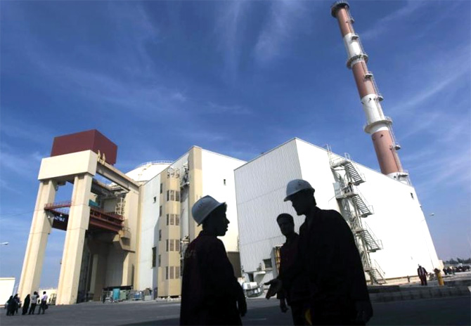 Iranian workers stand in front of the Bushehr nuclear power plant.