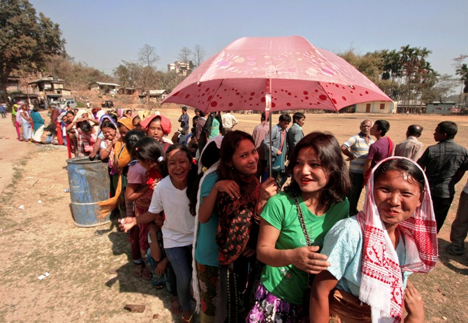 A woman shields herself from the sun with an umbrella as she and others queue to cast their vote at a polling station at Byrnihat, in the Ri-Bhoi district in the eastern Indian state of Meghalaya.