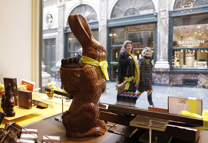 Two women walk past a chocolate Easter bunny at Belgian chocolate maker Neuhaus in Brussels, Belgium.