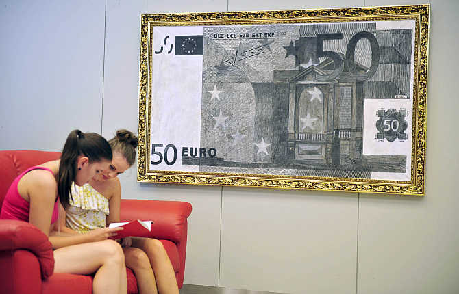 Women look through a catalogue near a painting of a Euro banknote during an exhibition by designer Alexsander Brezlan at the Faculty of Economics at the University of Ljubljana, Slovenia.
