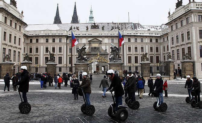 Tourists ride segways past Prague Castle, the Czech Republic.