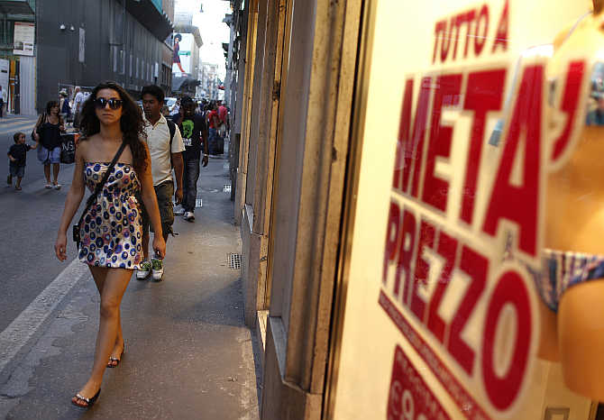 A woman walks in front of a shop window in downtown Rome, Italy.