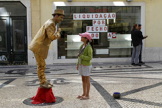 A girl looks at a performance artist in downtown Lisbon, Portugal.