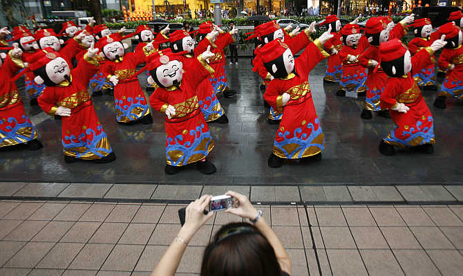 A bystander takes pictures as performers dressed as Chinese Fortune Gods dance during a flash mob in the Orchard Road shopping district in Singapore.