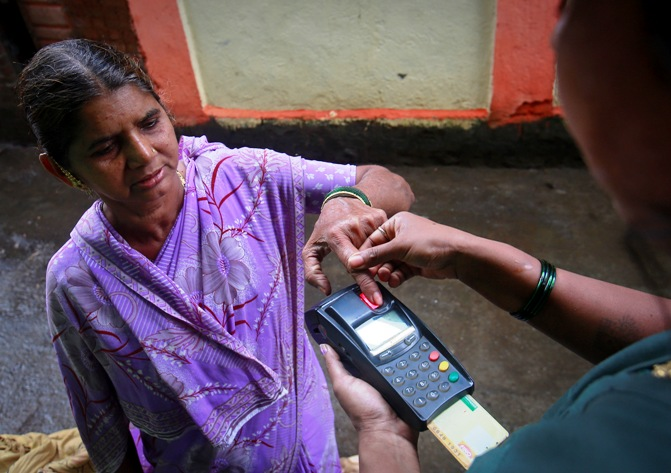 A customer gives her finger impression to update her smart card after she gave her money to a coordinator who works for Financial Information Network and Operations Ltd in Wavanje village of Raigad district.