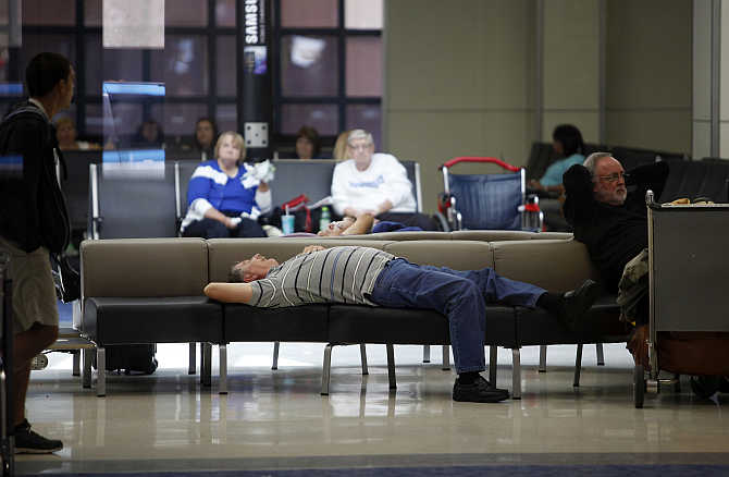 Passengers at Dallas/Fort Worth International Airport, Texas, rest before their flights.