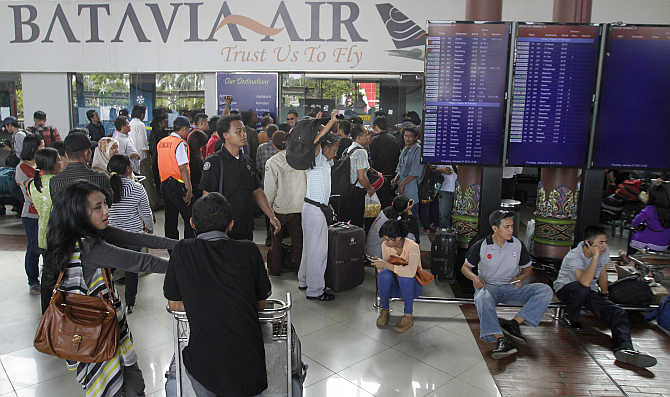 Passengers of Batavia Air gather in front of a ticket booth at the Sukarno-Hatta airport on the outskirts of Jakarta.