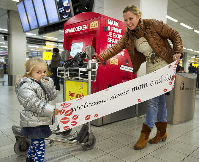 Two-year-old Luna and her aunt hold a banner at Amsterdam Airport Schiphol.