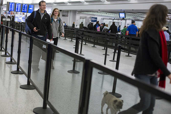 Travellers walk through a security line at John F Kennedy International Airport in New York.