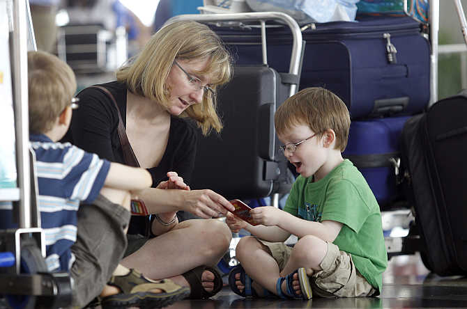 Lawrence Jones plays cards with his mother Susan Hourihan and brother Harvey as they wait for their flight to London, at Kuala Lumpur International Airport.